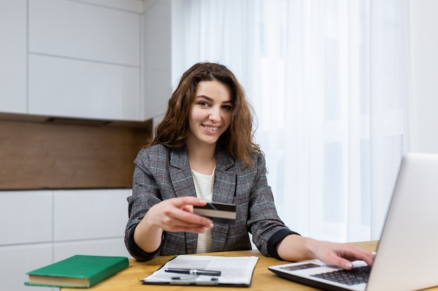 Die frau entspannt sich zu hause, kauft online ein, benutzt einen laptop und eine kreditkarte