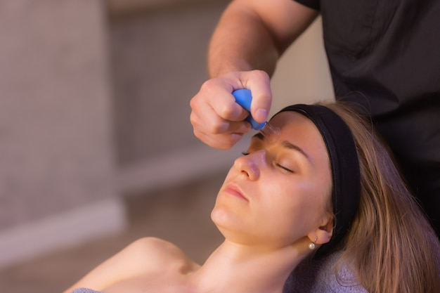 Die frau erhält eine gesichtsverjüngung mit schröpfmassage im akupunktur-wellness-spa.