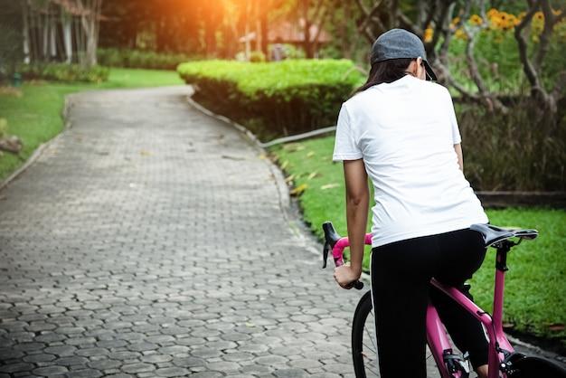 Die frau fährt fahrrad in einem park, verschwommenes licht herum