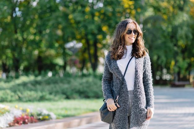 Die frau geht mit einem großen lächeln auf der straße. sie hat dunkle kurze haare und wundervolle große blaue augen. sie trägt einen grauen pullover und ein weißes hemd.