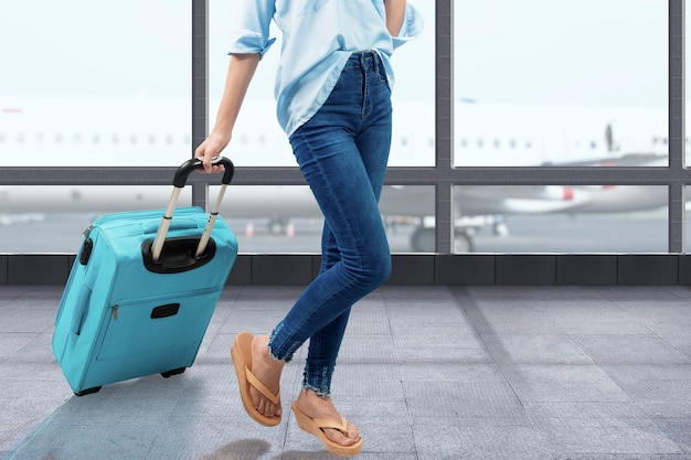 Die frau geht mit einem koffer auf dem flughafenterminal spazieren