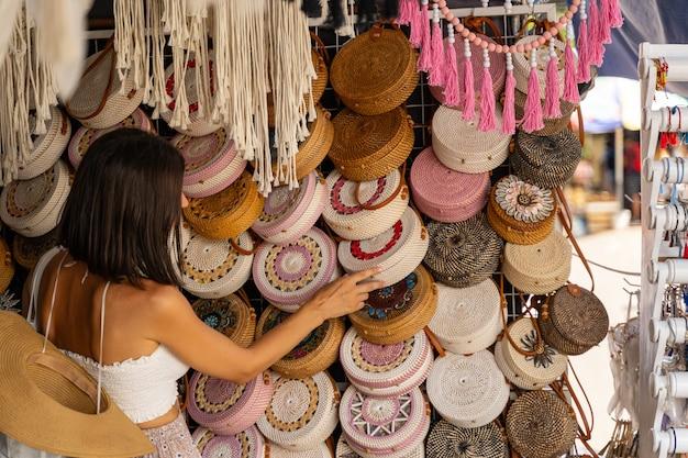 Die frau genießt ihre reise in ein exotisches land und schenkt sich in einem kleinen straßenladen ein geschenk zwischen korbtaschen