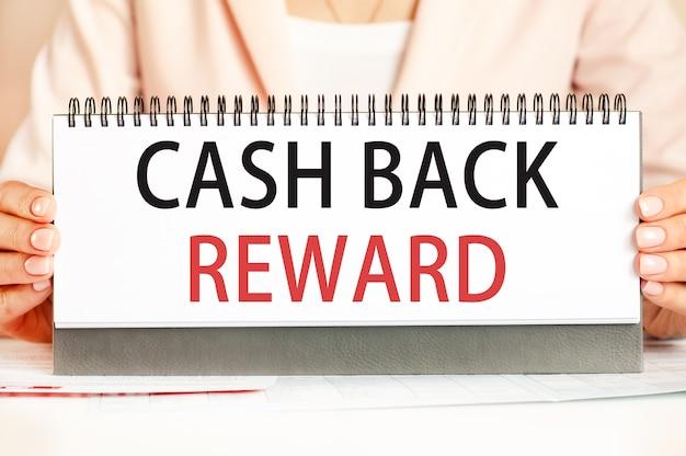 Die frau hält einen karton mit den händen mit dem text cash back reward
