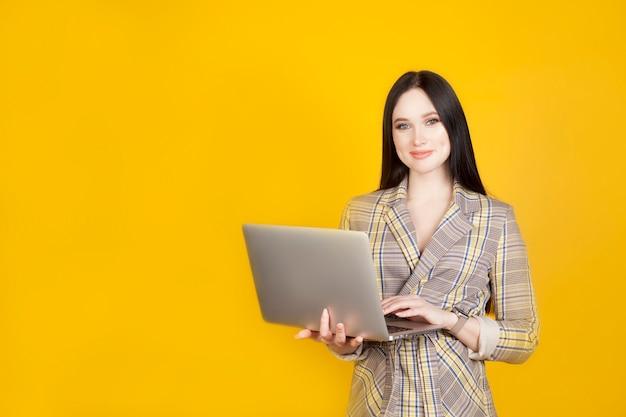 Die frau hält einen laptop mit einem hellen, freundlichen lächeln auf einem gelben hintergrund und kopiert platz. das konzept der arbeit am computer und moderne neue technologien.