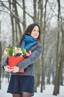 Die frau hält in ihren händen rote geschenkbox mit schönen blumenstrauß als geschenk zum valentinstag