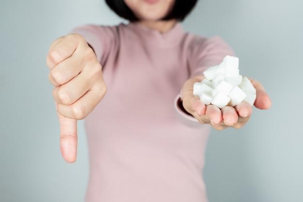 Die frau hielt einen zuckerwürfel in der hand und fühlte sich krank mit zuckerwürfeln.