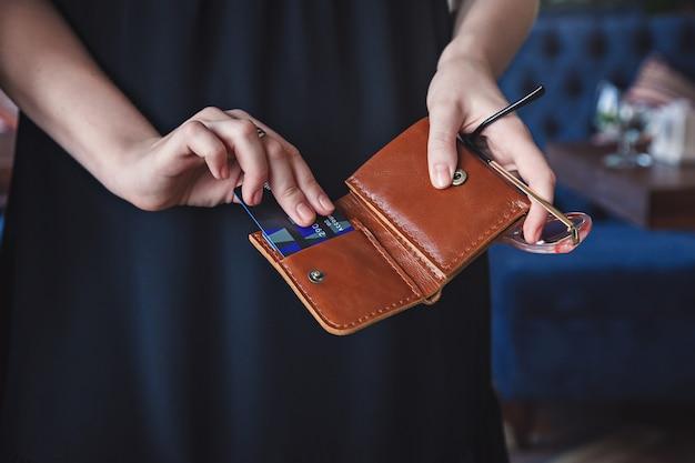 Die frau holt eine kreditkarte heraus