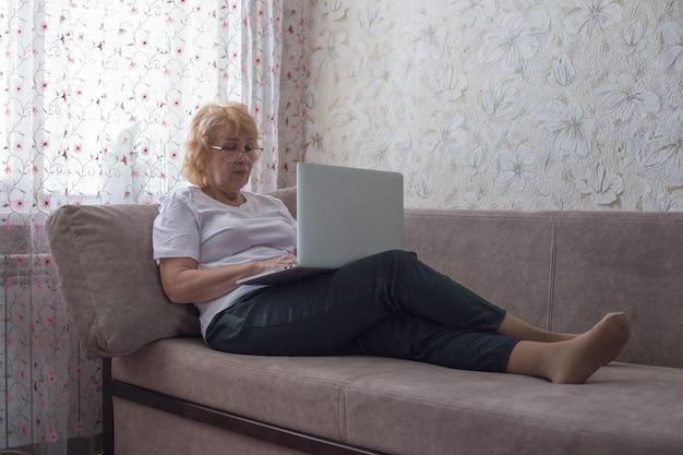 Die frau im ruhestand liegt mit einem laptop auf einem sofa. arbeit zu hause für ältere menschen