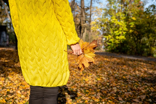 Die frau in der gelben jacke hält bunte blätter in den händen.