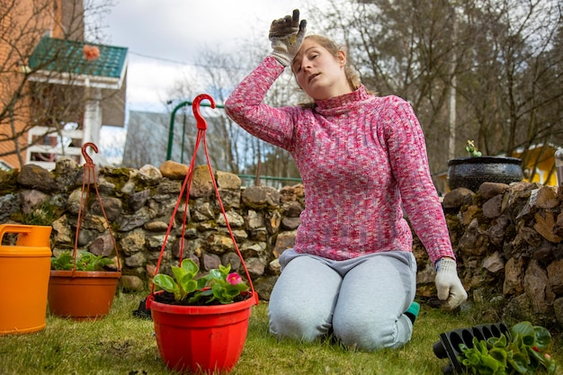 Die frau ist es leid, pflanzen in töpfen zu pflanzen, müde frau, die im hinterhof im garten arbeitet