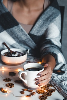 Die frau ist in eine decke gewickelt und hält eine tasse kaffee in den händen. winterkomfort, girlanden, weihnachtsstimmung.