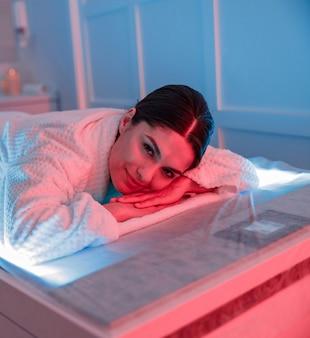 Die frau kümmert sich um ihre haut und macht kosmetik- und laserverfahren