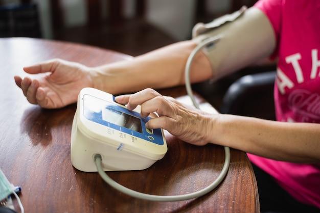 Die frau kümmert sich um ihren gesundheitszustand, indem sie ihren blutdruck kontrolliert