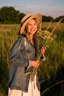 Die frau lacht und hält einen strauß wildblumen in der hand