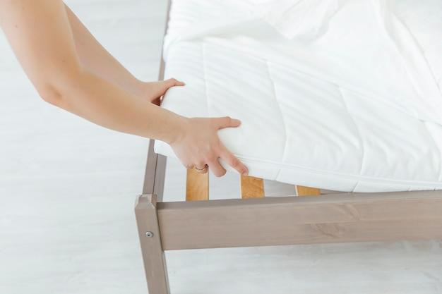 Die frau legt den bettbezug oder die matratzenauflage auf das bett oder legt sie zum reinigungsprozess ab