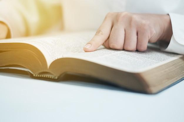 Die frau liest die bibel im raum.