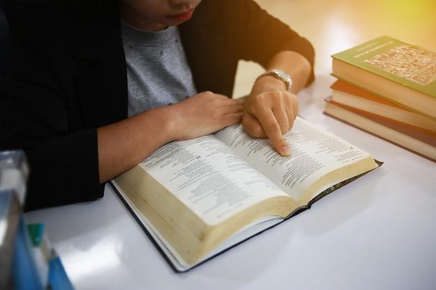 Die frau liest in den werken die bibel.