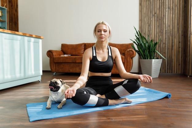 Die frau meditiert, der hund ruht in der nähe