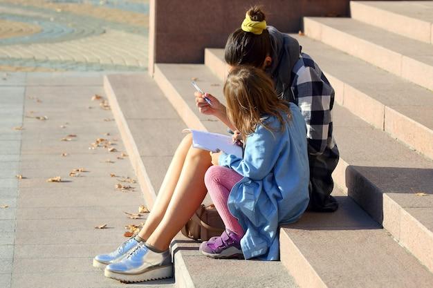 Die frau mit dem kleinen mädchen, das in einem notizbuch zeichnet, während sie auf der treppe sitzt
