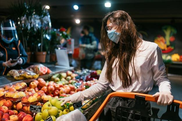 Die frau mit der op-maske wird äpfel kaufen