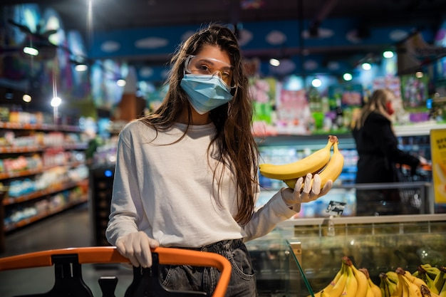 Die frau mit der op-maske wird bananen kaufen