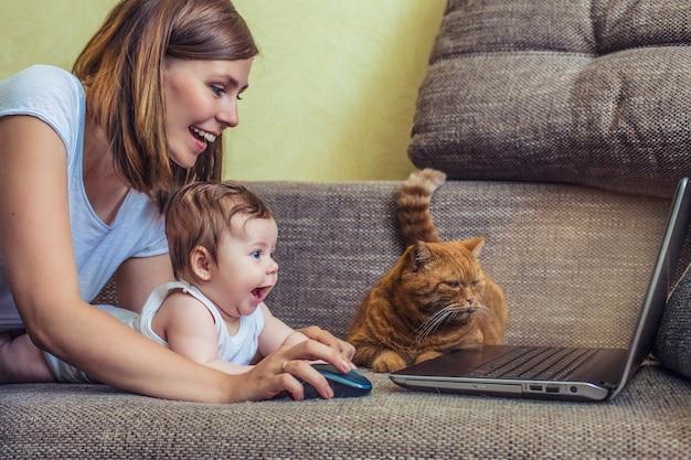 Die frau mit einem baby und einer katze am laptop liegt auf der couch