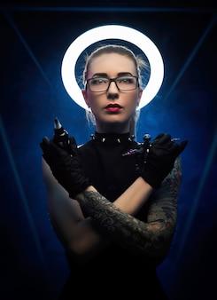 Die frau mit einem heiligenschein in schwarzer kleidung mit einer tätowiermaschine