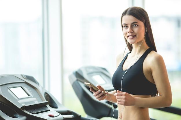 Die frau mit kopfhörer hält ein telefon im fitnessclub