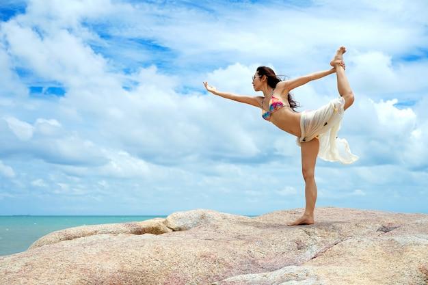 Die frau mit yoga-haltung am strand