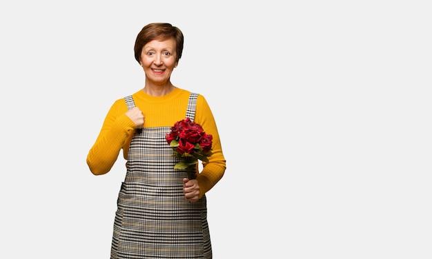 Die frau mittleren alters, die den valentinsgrußtag überrascht feiert, fühlt sich erfolgreich und wohlhabend