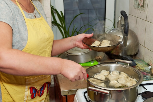 Die frau nimmt gekochte heiße knödel aus der pfanne in einen transparenten teller. hausmannskost