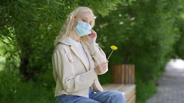Die frau nimmt ihre medizinische maske ab und schnuppert am gelben löwenzahn. erholung im freien während einer epidemie. 4k uhd