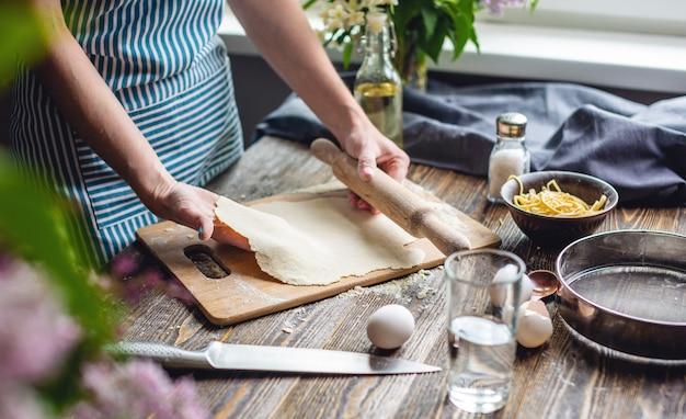 Die frau rollt frischen teig aus, um in gemütlicher atmosphäre pasta zu machen