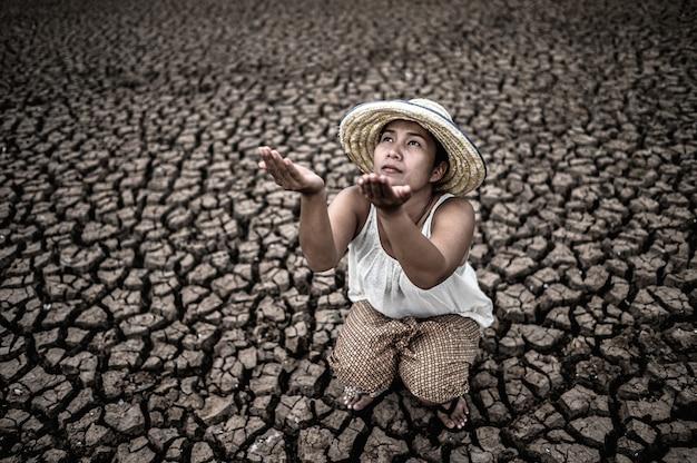 Die frau saß am himmel und bat um regen bei trockenem wetter und globaler erwärmung