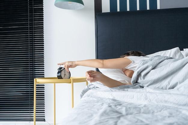 Die frau schaltet den nervigen wecker aus, um weiter zu schlafen. schlaf noch ein bisschen. es ist ein harter morgen. zeit aufzuwachen.