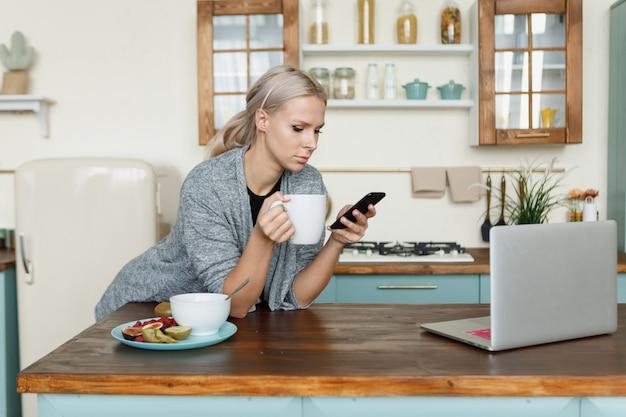 Die frau schaut auf den telefonbildschirm und frühstückt. der laptop liegt auf dem tisch. morgens von zu hause aus arbeiten