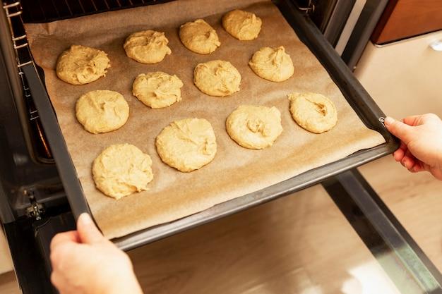 Die frau schickt ein backblech mit rohen keksen zum backen in den ofen.