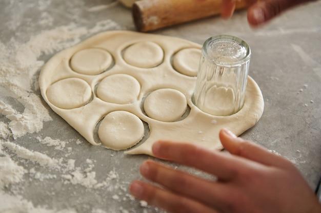 Die frau schneidet die runden formen mit einem glas für ravioli oder knödel aus. teig im fokus