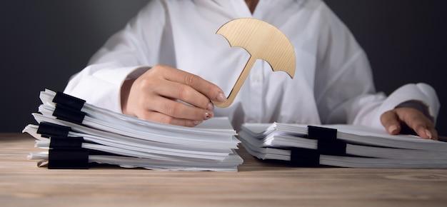 Die frau schützt die dokumente mit einem regenschirm