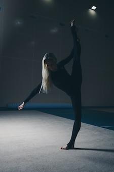 Die frau setzte sich auf die schnur. unterricht im fitnessclub. das mädchen ist in der freizeitgymnastik beschäftigt. sportübungen und stretching: leichtathletik