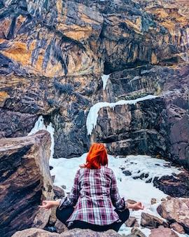 Die frau sitzt auf dem felsenberg. junge yogafrau sitzen meditation auf bergspitzenfelsen.