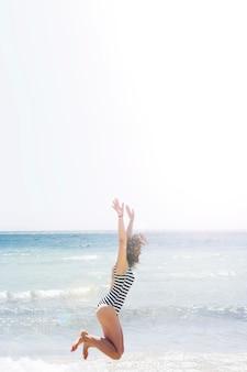 Die frau springend in den strand