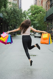 Die frau springend mit einkaufstaschen