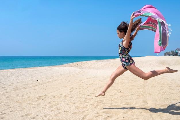 Die frau springend mit strandverpackung