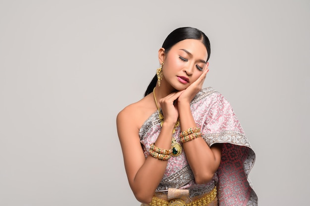 Die frau trägt ein thailändisches kleid und die hände berühren das gesicht.