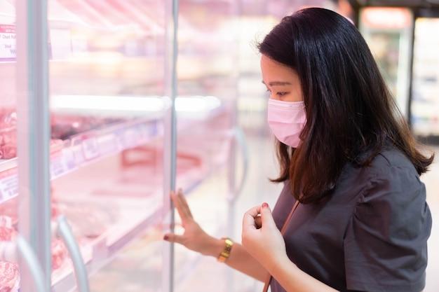 Die frau trägt eine schutzmaske und steht vor dem gefrierschrank, um sich für fleisch zu entscheiden