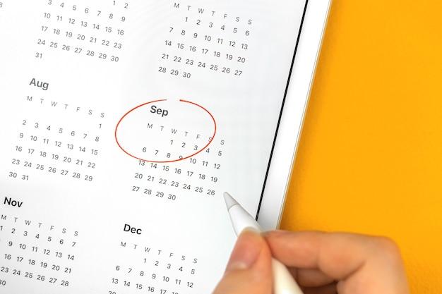 Die frau verwendet die kalender-app auf dem tablet und ist im roten septembermonat eingekreist, nahaufnahmefoto