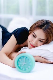 Die frau wachte morgens mit einem strahlenden lächeln auf. und ein wecker auf dem bett