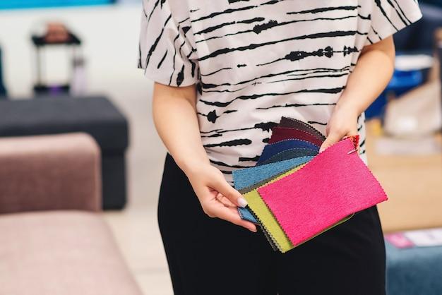 Die frau wählt die farben und muster der möbelstoffe. hintergrund der textilindustrie. gewebekatalog. junge frau wählt den stoff für das neue sofa. stoffmuster zum polstern des sofas.