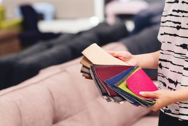 Die frau wählt die farben und muster der möbelstoffe. hintergrund der textilindustrie. gewebekatalog.
